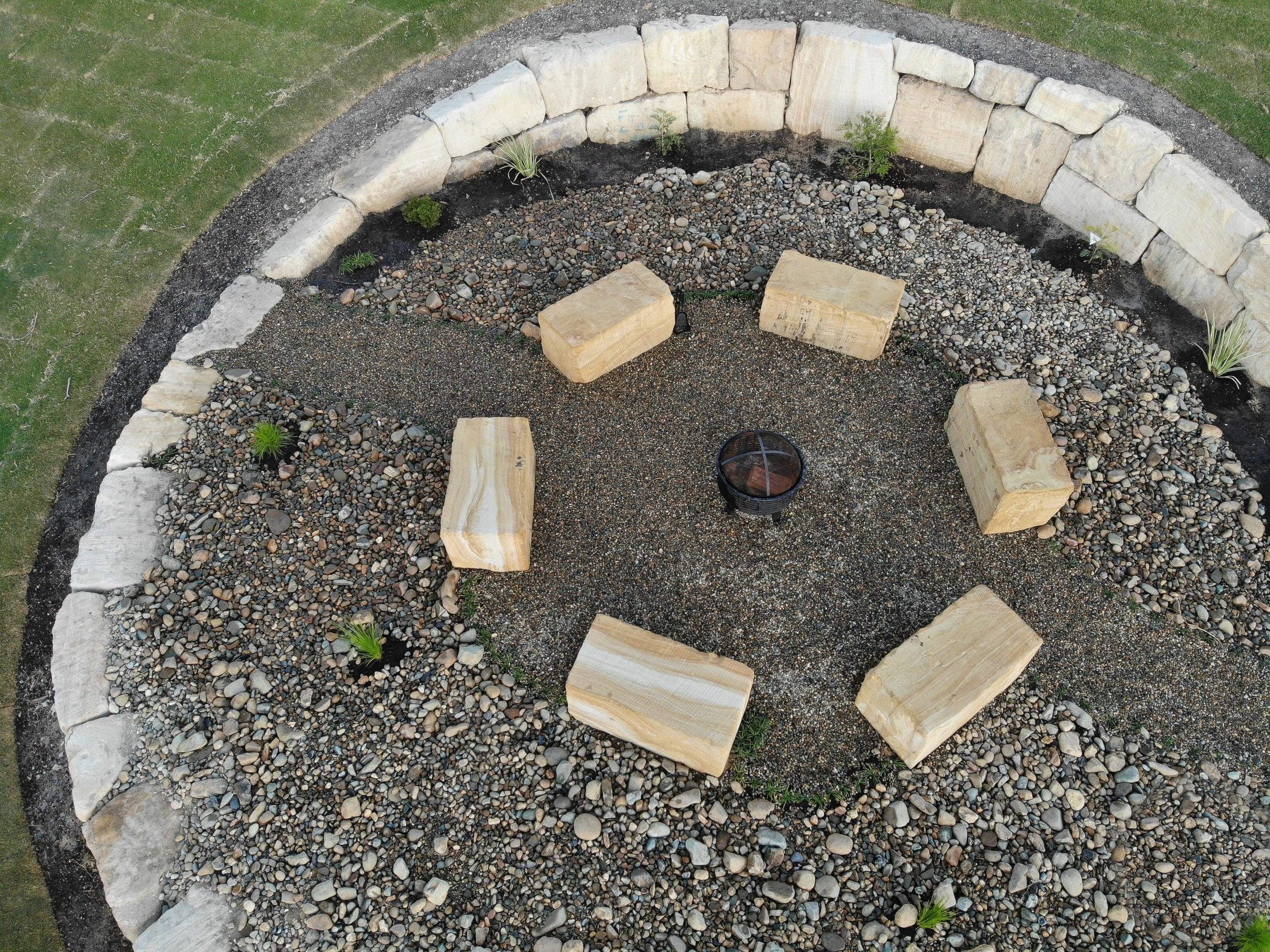 Drone footage of sandstone fire pit, wall and seating.
