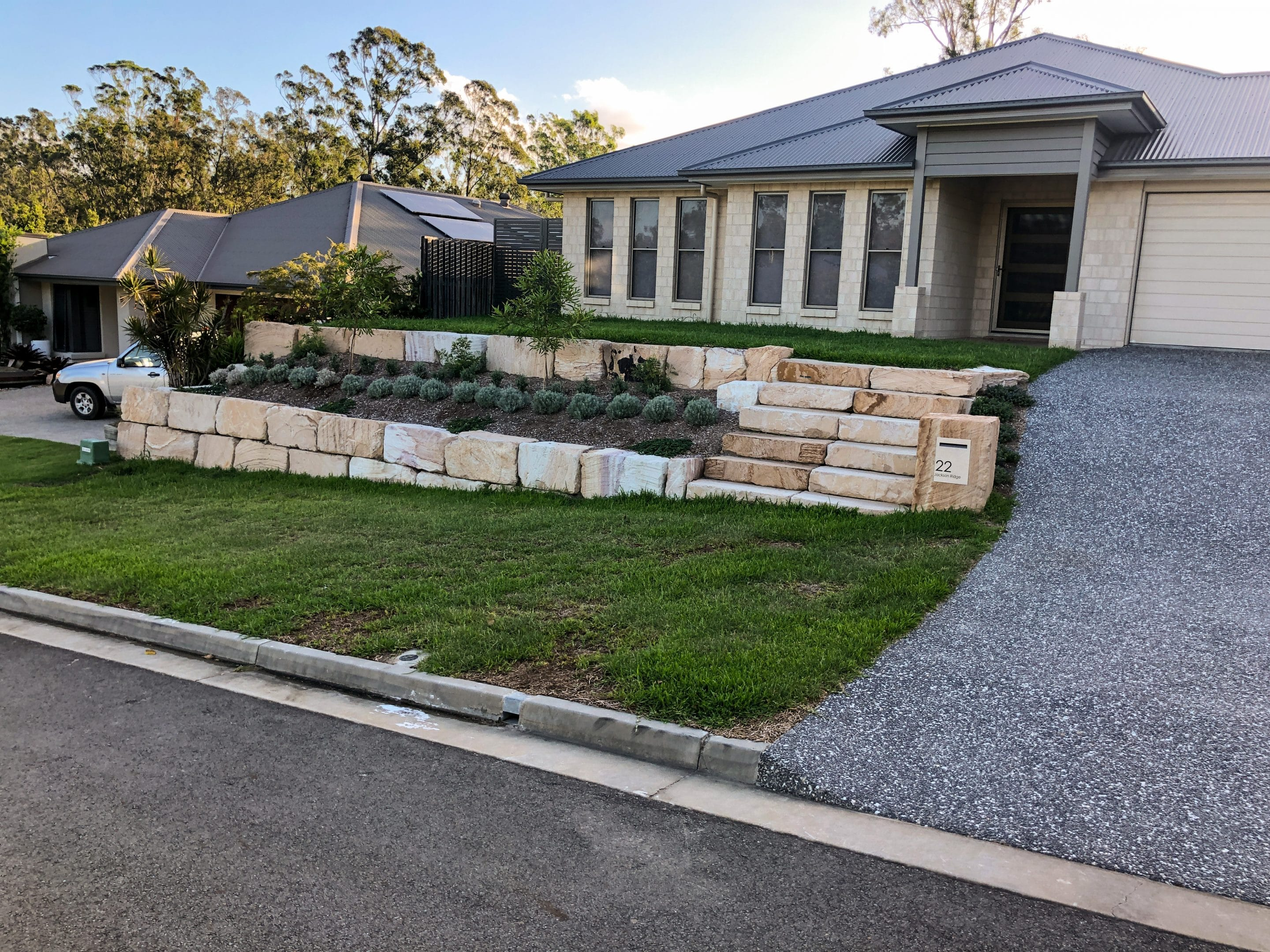 A beautifully designed rock wall made out of B grade sandstone, the wall is double tiered and is complemented by a sandstone letterbox and steps.