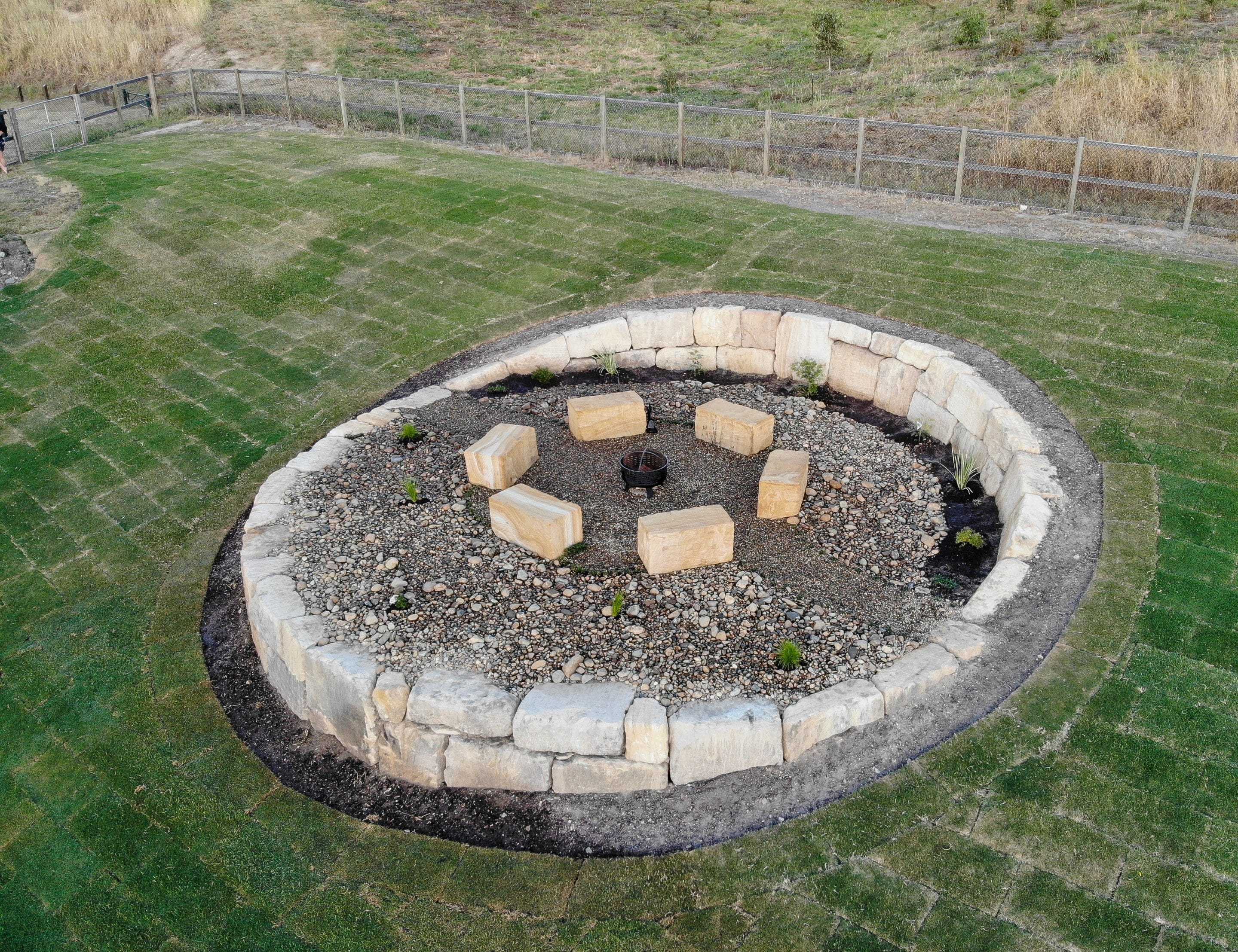 C grade sandstone retaining wall with free-standing sandstone seating, sandstone fire pit