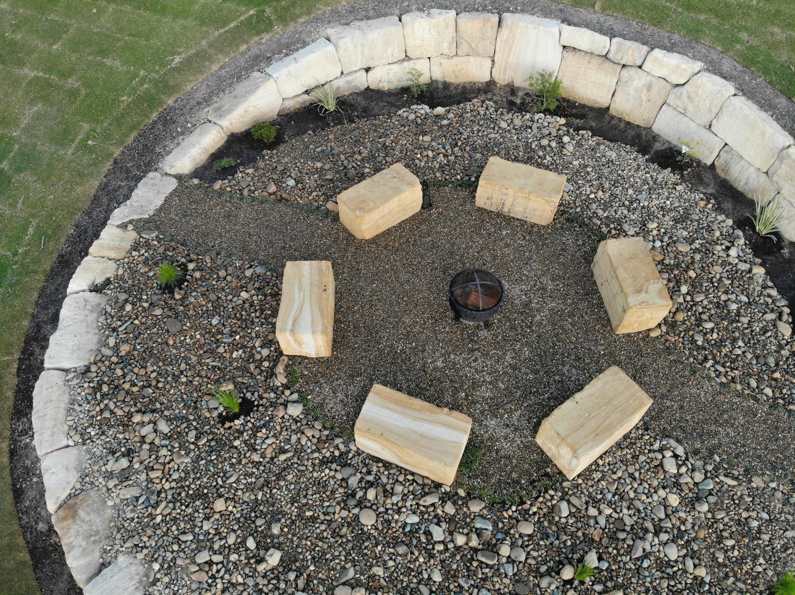 C grade sandstone retaining wall with free-standing sandstone seating, sandstone fire pit, rock wall Gold Coast