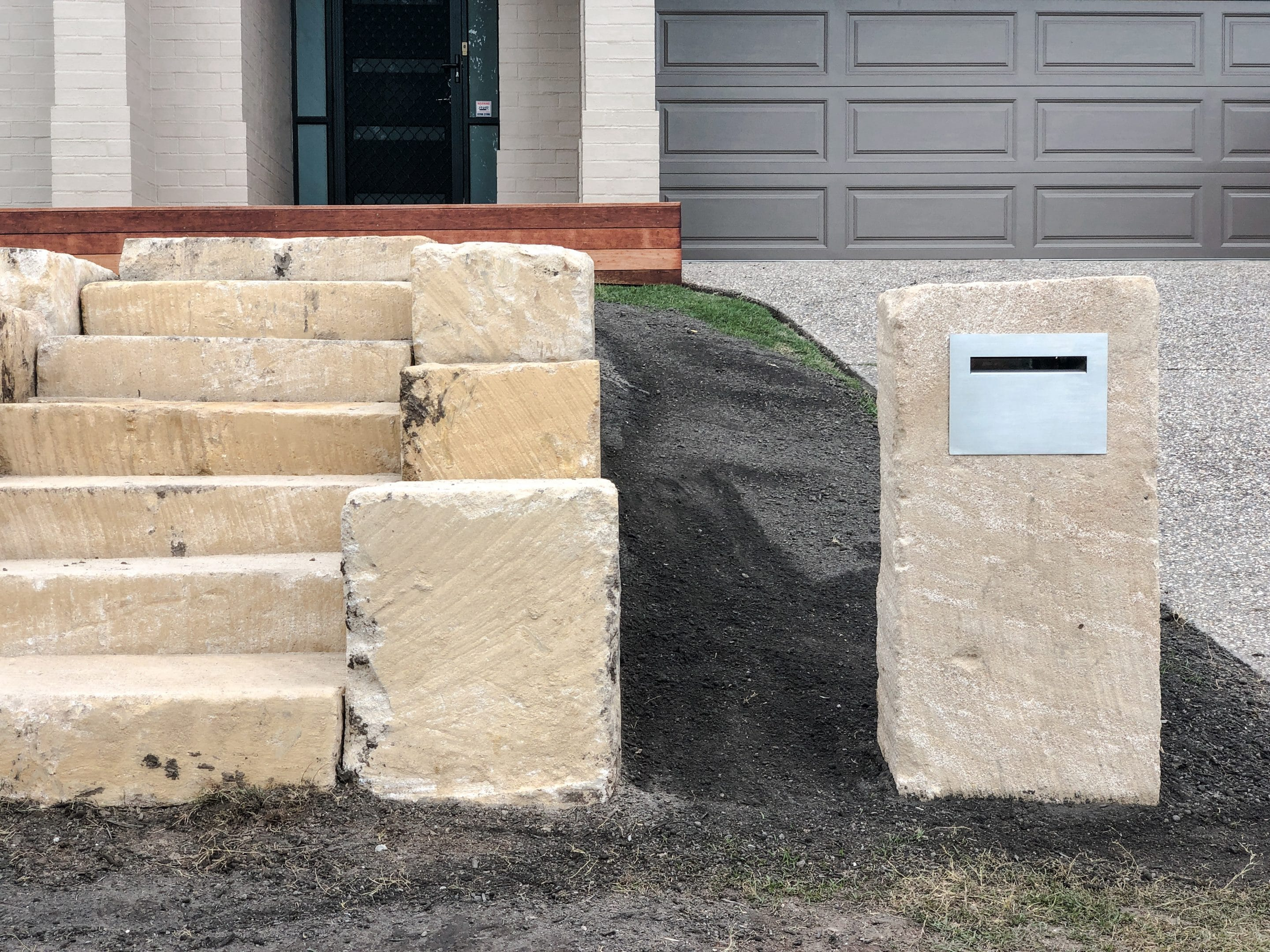 Custom sandstone letter box and rough sawn sandstone steps Gold Coast