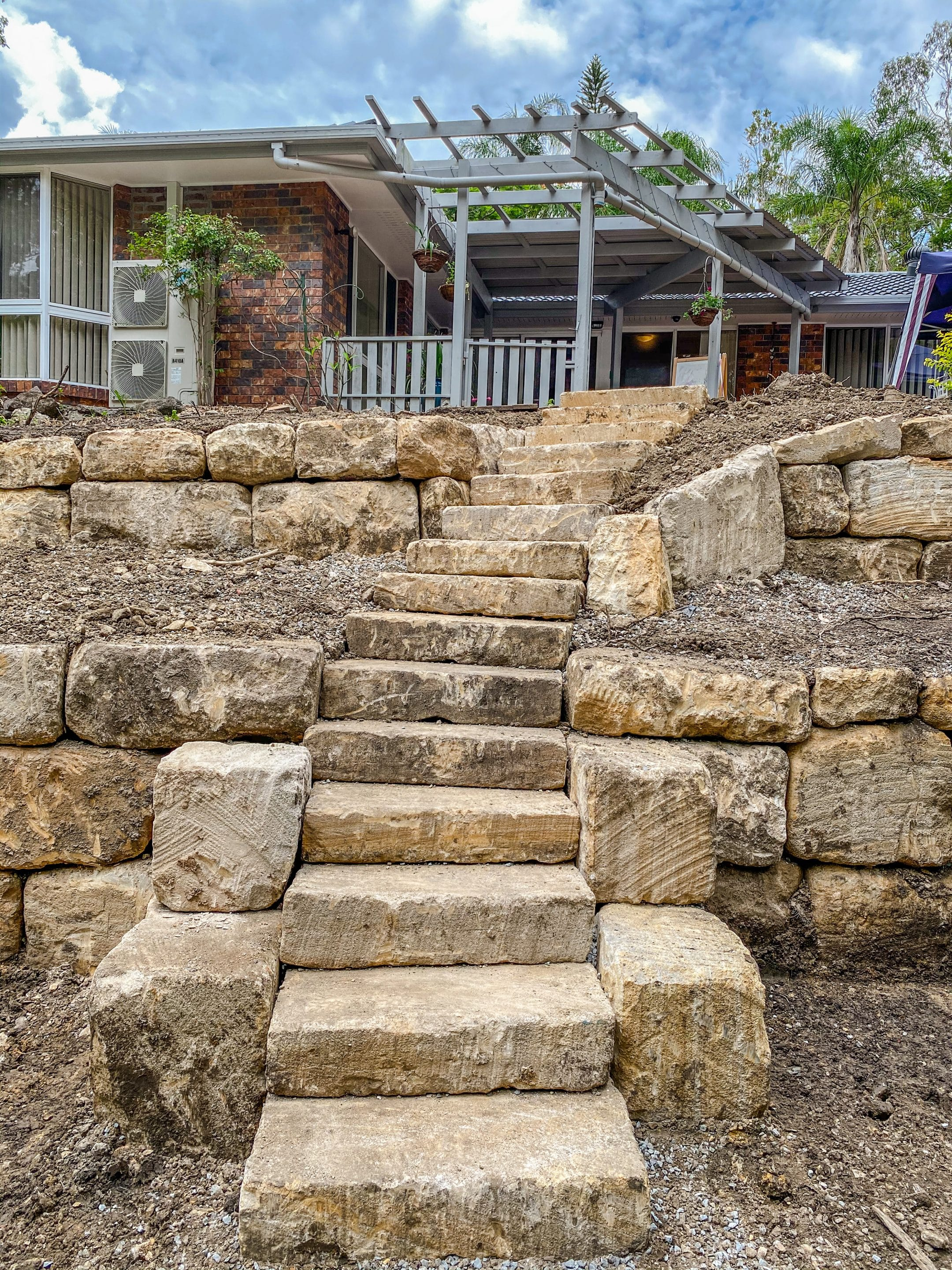 Rough sawn sandstone steps and c grade rock wall, retaining wall Gold Coast