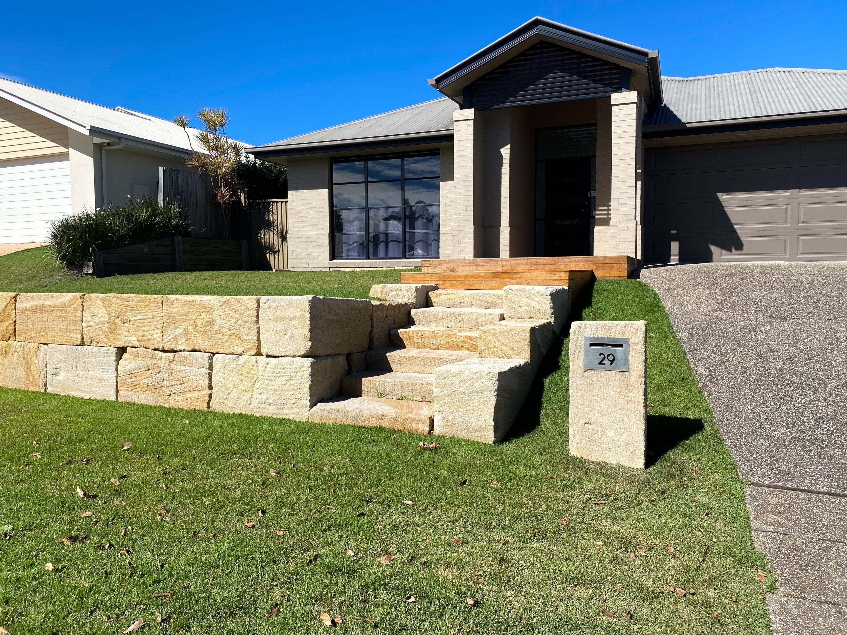 A grade sandstone retaining wall, custom sandstone letter box, sandstone steps - rock wall Gold Coast